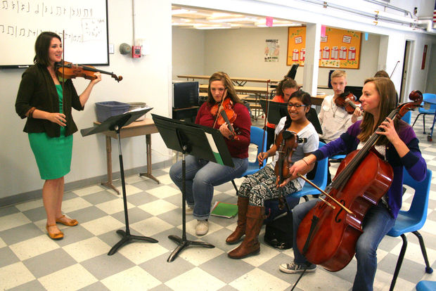 "Music instructor Emily Athman has 34 students in the high school orchestra class – so large they are too big for her classroom and the students set up in the lunch room, between meals. ""We make the most of our time available,"" said Athman. ""The students set up the rehearsal space and then reset for lunch."""
