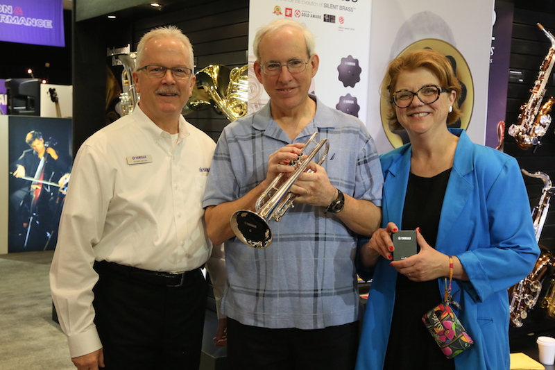 Belleville, Illinois residents William and Cynthia Shirley, winners of the Yamaha Silence is Golden contest winners, holding a SILENT Brass practice system for trumpet at the 2015 NAMM Show in Anaheim, California, the largest musical instrument trade convention in North America. During their all-expenses paid, four day and five night stay, the couple also visited Disneyland Park and Disneyland California Adventure Park. Standing to their left, Roger Eaton, director of marketing, Yamaha Corporation of America, Band & Orchestral Division.
