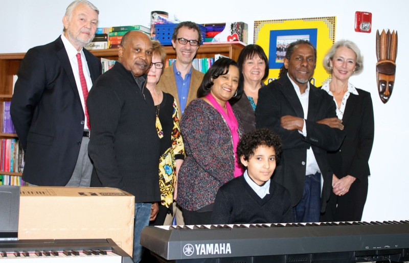 (L-R): Ken Albrecht, founder of the Carter Albrecht Music Foundation, Johnny Harris, store manager Metroplex Piano Dallas, Judy Albrecht, Founder CAMF, Salah Boukadoum, board member CAMF and Founder and CEO of Good Returns, Karen Harkey, Director at Choice Leadersihp Academy, Janis Evans, Trumpets4Kids board member, Freddie Jones, Founder and Artistic Director of Trumpets4Kids, Lynn Nikaidoh, supporter of CAMF. At the keyboard: Maphios Mekbeb-Gillette, student at Choice Leadership Academy.